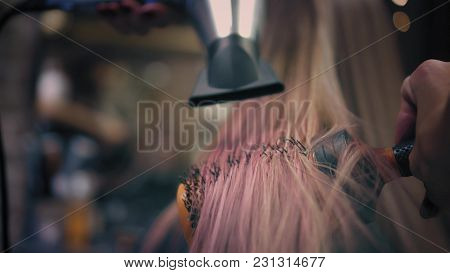 Hairdresser Is Strighten Woman's Long Pink Blonde Hair With Hair Dryer And Round Professional Hairbr
