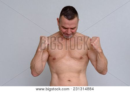 Naked Mature Man Clenching Fists Triumphantly