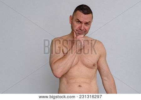 Portrait Of Naked Mature Man Looking Quizzical