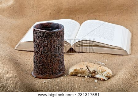 Bible, Chalice And Bread On The Textile Tablecloth.