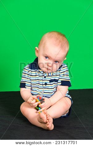 Sad 10 Month Old Baby Boy On Green Screen Playing With Toy