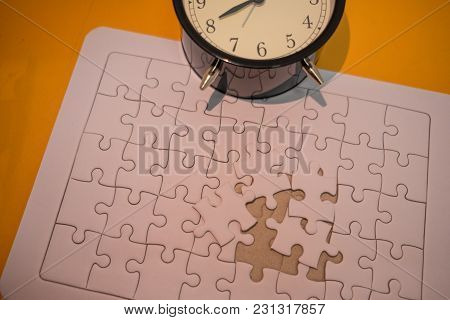 Business Background White Jigsaw Placed On Orange Table With Clock And Copy Space. Image For Texture