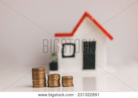 Coins Stacked With A Blurred House On The Background: Real Estate, Property Investment, House Mortga