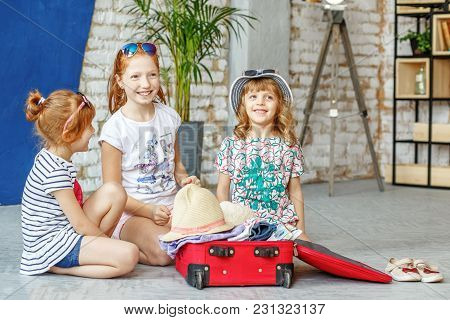 Three Happy Children Of Girls Pack A Suitcase On A Trip. Concept Tourism, Trip, Vacation, Rest, Sea.