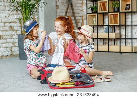 Three Happy Kids Of Girls Pack A Suitcase On A Trip. Concept Tourism, Trip, Vacation, Rest, Sea.