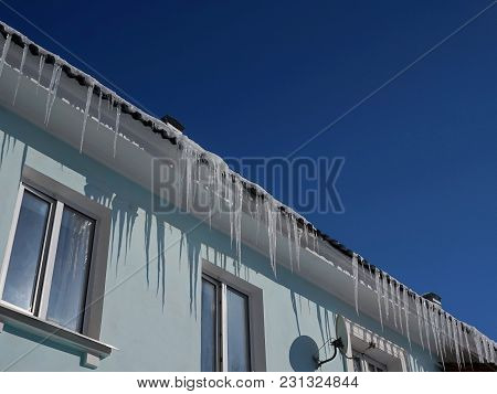 The Roof Of An Old House. Large Icicles. Sunny Day. Clear Blue Sky.