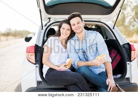 Happy Young Couple Sitting In Car Trunk With Sandwiches During Road Trip