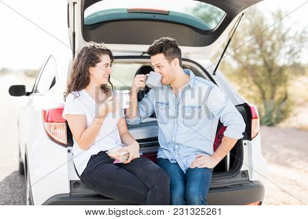 Happy Young Couple Having A Coffee Break During Road Trip In Countryside.