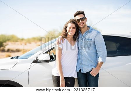 Portrait Of Beautiful Young Couple Standing Together Near Car Outdoors And Smiling While On Road Tri