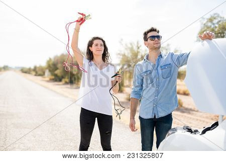 Couple Standing On The Road With Breakdown Car, Woman Calling For Help Holding Battery Wire To Jump