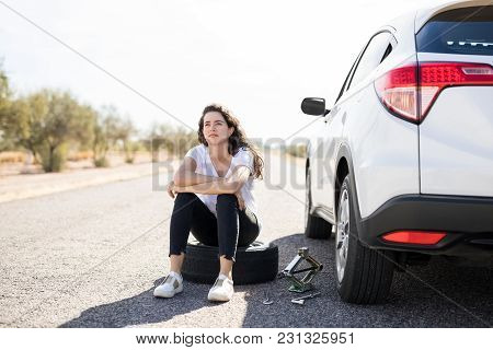 Portrait Of Upset Young Woman Sitting On Spare Tyre On Road While Changing The Flat Wheel Of Her Car