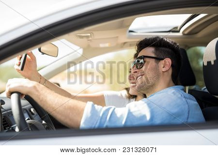 Side View Of A Young Man Driving Car With Girlfriend Taking Selfie With Smartphone