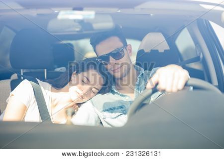 Portrait Of A Handsome Young Man Driving A Car While His Girlfriend Falls Asleep On His Shoulder