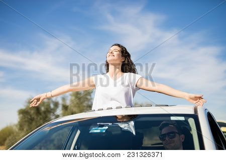 Front View Of Young Caucasian Woman With Arms Outstretched Standing Out Of Sunroof Of Car With Man D