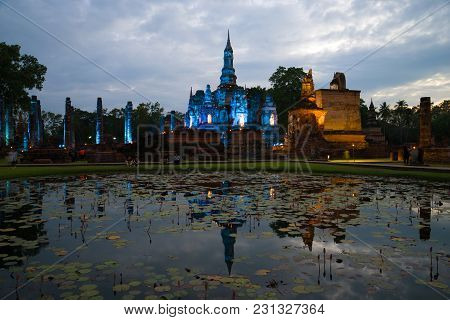 Ruins Of The Buddhist Temple Of Wat Mahathat In Blue Illuminated By A Cloudy Evening. Sukhothai Hist