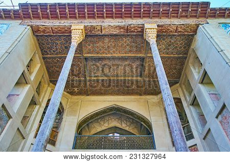 Isfahan, Iran - October 20, 2017: The  Carved Wooden Ceiling And Slender Pillars Of The Porch Of Has