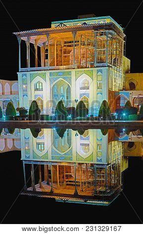 The Night Lights In Naqsh-e Jahan Square, Medieval Qapu Palace Is Reflected In Black Mirror Of The F