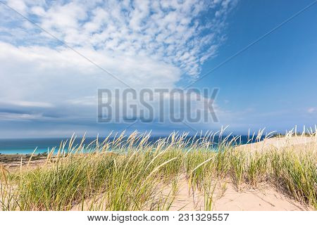 Dune Grass Sways In The Breeze Under A Blue Sky With Dramatic White Clouds Streaking Overhead At Sle