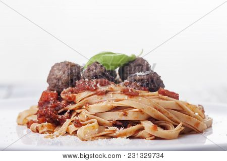 Spaghetti With Tomato Sauce And Meatballs On A Plate
