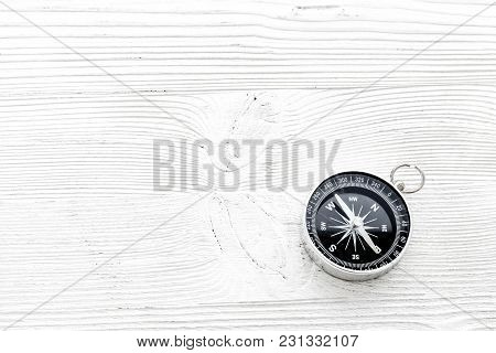 Compass On White Wooden Desk Background Top View Copy Space.