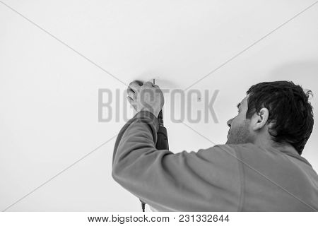 Greyscale Image Of A Workman Using A Handheld Electric Drill To Drill A Hole In The Ceiling Of A Bui