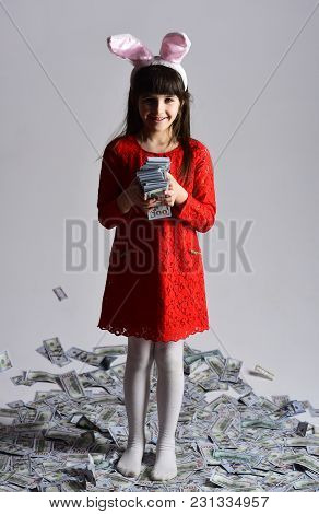 Business Success, Childhood, Happy Easter. Small Girl Child In Bunny Ears With Many Dollars Money. F