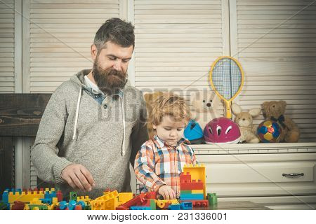 Dad And Kid With Busy Faces Make Brick Construction. Fatherhood Concept. Father And Son Play Togethe