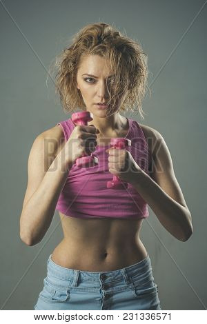 Woman Coach With Concentrated Face Holds Dumbbells ?n Grey Background. Sportive Woman Concept. Girl