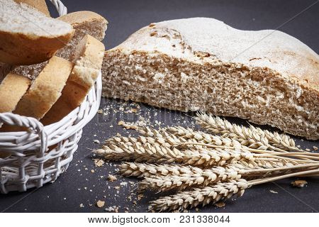 Fresh Bread, Slices Of Sliced Bread In Basket And Wheat Ears On Black Background. Bread And Crumbs O