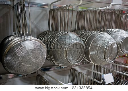 Many Rows Of Silver Metal Colanders And Strainers Hanging On Metal Rack In Wholesale Store.