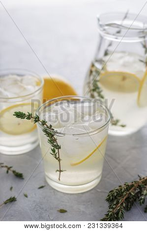 Two Glasses With Homemade Lemonade And Thyme On The Stone Table.