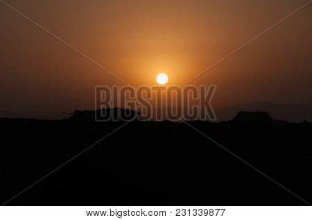 Sunset In The Sahara: The Dark Lower Part Of The Frame, Above The Orange Bright Sky With A Ball Of L