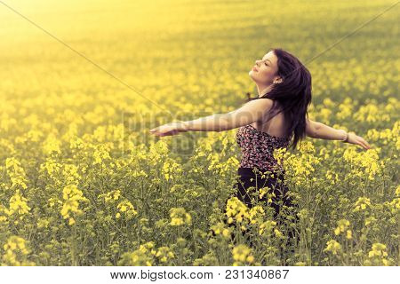 Beautiful Woman In Meadow Of Yellow Twist From Behind. Attractive Authentic Young Girl Enjoying The