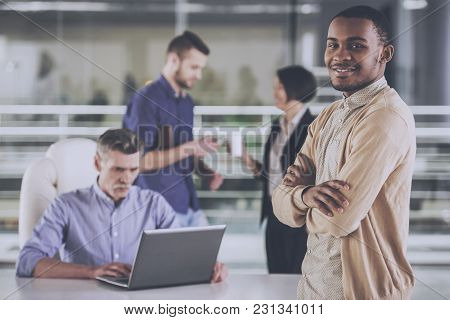 Young African Businessman Standing With Crossed Hands Business People On Background.