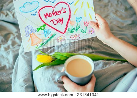 Young Mother Get Surprise Present For Mother Day In Bed. Woman Hold Picture Of Her Child For Mother