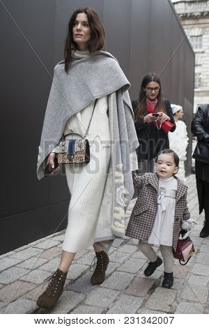 London - February 18: Brunette Woman In A White Suit And Black Poncho Holds Hand Of A Little Girl In