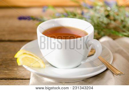 White Cup Of Tea With A Saucer, With A Lemon In The Sun Is On A Wooden Table