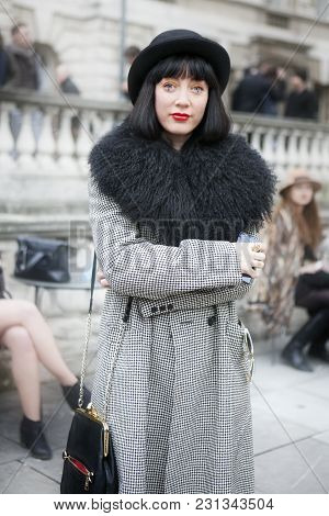 London - February 18: Stylish Brunette Woman In White Black Coat And Black Hat  During London Fashio