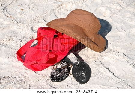 Red Beach Bag, Hat And Flipflops Laying In The Sand On The Beach
