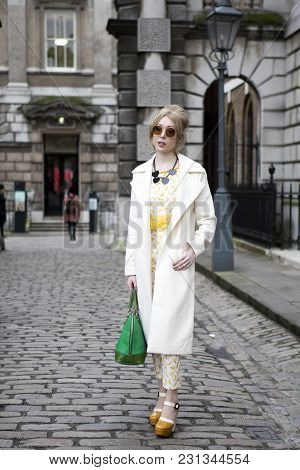 London - February 18: Blond Woman In White Coat And Yellow Dress Poses For Photographers With Silver