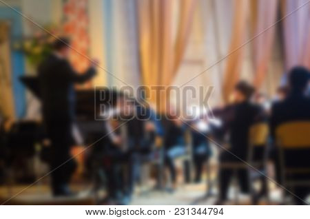 Orchestra Conductor Manages The Orchestra. Musical Concept. Blurred Background. Background For Desig