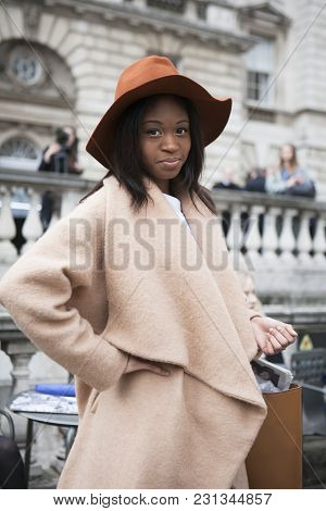 London - February 18: Brunette Woman In Beige Coat And Orange Hat Poses For Photographers With Silve