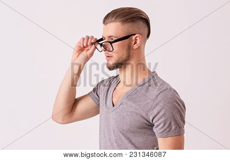 Side View Of Young Business Expert Wearing Eyeglasses And Looking Away While Isolated On White Backg