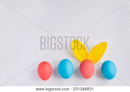 Happy Easter Concept. Big Colorful Eggs With Furry Bunny Ears Isolated On White Background. Top View