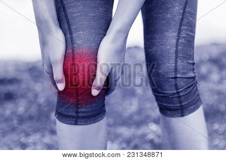 Injuries - sports running knee injury woman. Girl runner with pain, from sprained knee. Closeup of leg, and knee outdoors. Arthritis athlete.