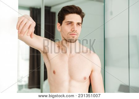 Portrait of a serious naked man standing in home looking aside.