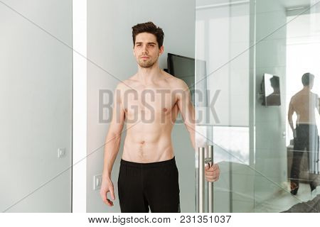 Portrait of a serious naked man standing in home indoors looking aside.