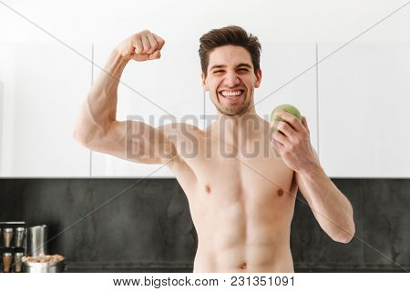 Portrait of a happy cheerful naked man sportsman standing in kitchen in home showing biceps holding apple looking camera.