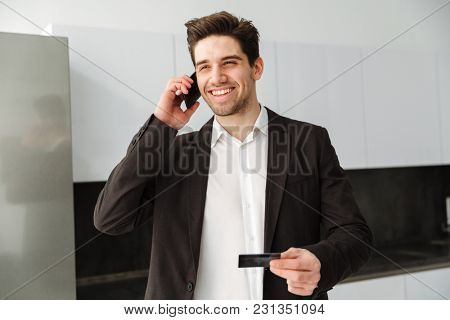 Photo of happy young businessman standing in home indoors. Looking aside talking by mobile phone holding credit card.