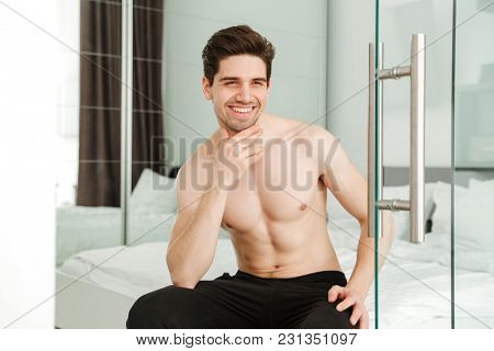 Portrait of a happy cheerful naked man sitting on bed in home looking camera.